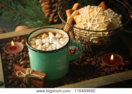 Mug of hot cacao with marshmallow and cookies on coffee beans
