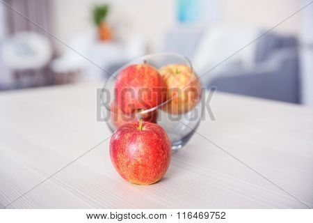 Apples in a glass bowl on wooden table, close up. Stylish kitchen interior.
