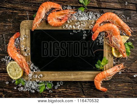 Prawns served on wood with blackboard