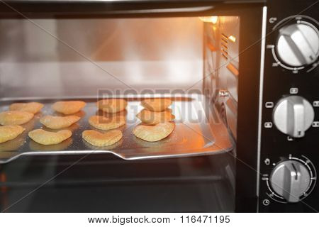 Uncooked heart shaped biscuits on a baking tray in an oven