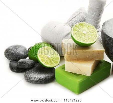 Spa composition with soap, sea salt, pebbles and lime, close up