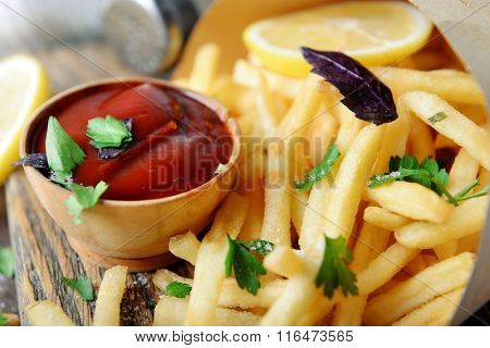 French fried potatoes in craft paper on cutting board
