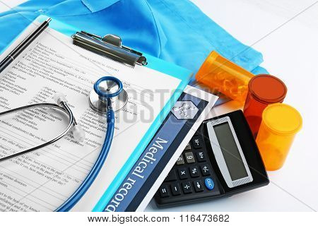 A stethoscope, calculator and clipboard, close-up