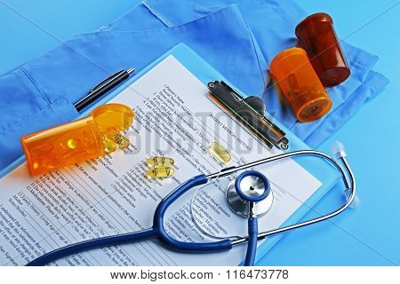 Medical stethoscope, clipboard, coat and pills, close-up