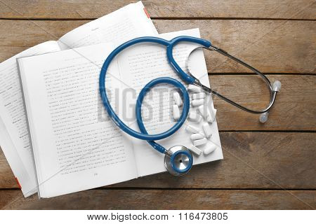 Stethoscope with pills and book on wooden table
