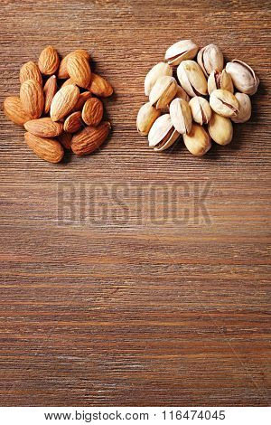 Two piles of pistachios and almonds on the wooden table