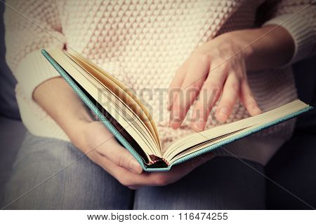 Woman  reading book at home, close up