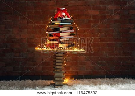 Christmas tree made of books on table on brick wall background