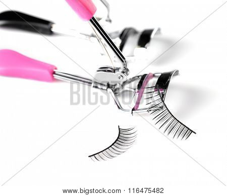 Two curlers and false eyelashes, isolated on white