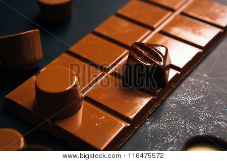 Many Chocolate Candy Sweets On Black Background