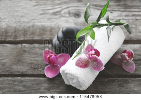 Spa stones with towel, bamboo and purple orchids on wooden background
