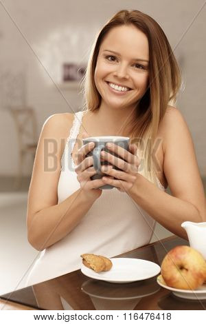 Young woman having morning tea, smiling happy, looking at camera.