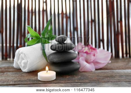 Spa stones with towel, candle, bamboo and pink orchid on wooden background