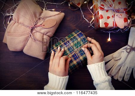 Female hands decorating Christmas gift box