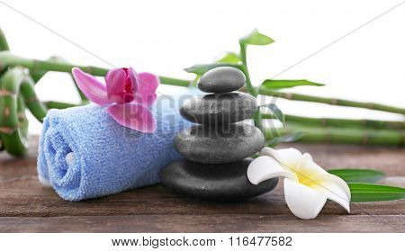 Spa stones with towel, tropical flowers and bamboo on white background