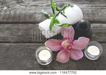 Spa stones with candles, towel, pink orchid and bamboo on wooden background
