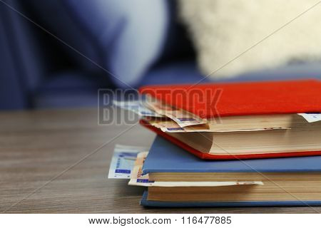 Red and blue books with hidden euro banknotes on wooden table