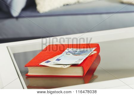 Red book with euro banknotes on glass table