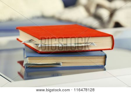 Red and blue books with hidden dollar banknotes on glass table