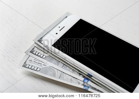 Smart phone on a stack of dollar banknotes over light table. Internet earning concept