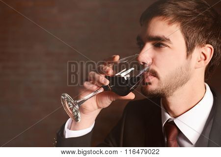 Man testing red wine in glass on brick wall background