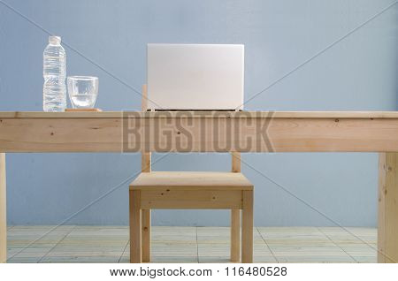 Office Table With Notebook And Natural Mineral Water. View From Front With Table Space.