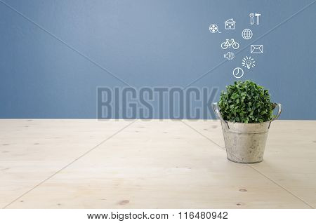 Wooden Desk With Dried Tree On Basket And White Symbol, View From Front With Green Leaf.