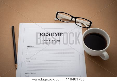 Office Desk With Resume Information, Coffee Cup, Black Pencil And Glasses.
