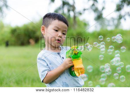 Little boy holding bubble blower gun