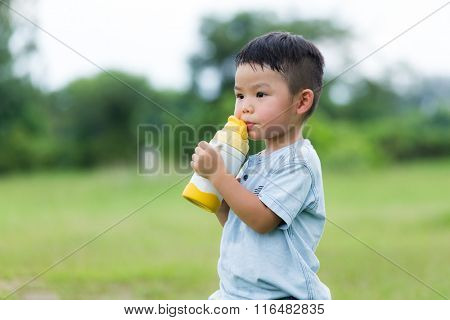 Little boy drink of water with plastic bottle
