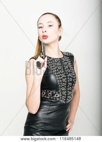 girl in black leather dress with braided hair is holding a gun
