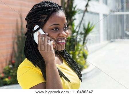 Cute African American Woman In A Yellow Shirt Listening At Mobile Phone