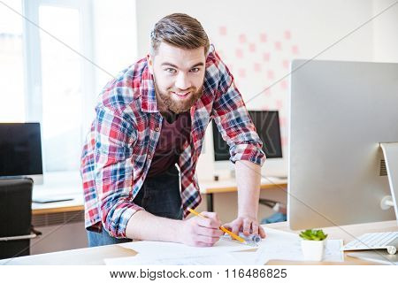 Smiling attractive bearded man in plaid shirt standing and working on blueprint in office
