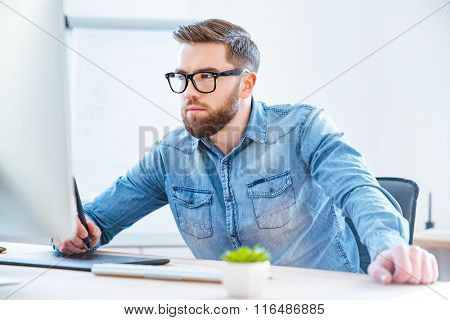 Serious concentrated young man designer drawing with graphic pen tablet using stylus in office
