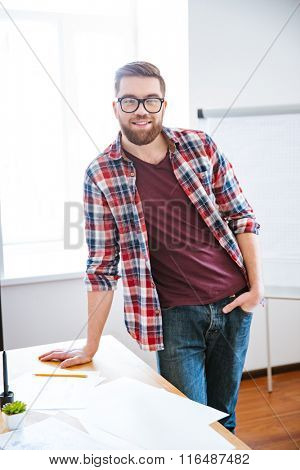 Confident happy bearded man in checkered shirt and jeans standing in office near flipchart