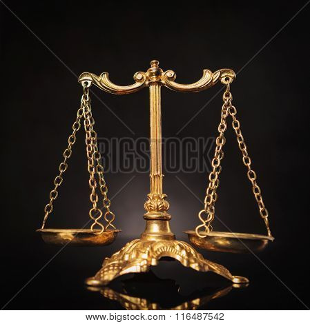 Symbol of justice, golden law scales on dark studio background