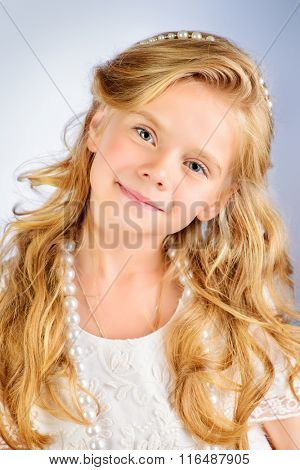 Portrait of a pretty little girl with beautiful blonde hair looking to camera and smiling. Kids fashion. Cosmetics, accessories.