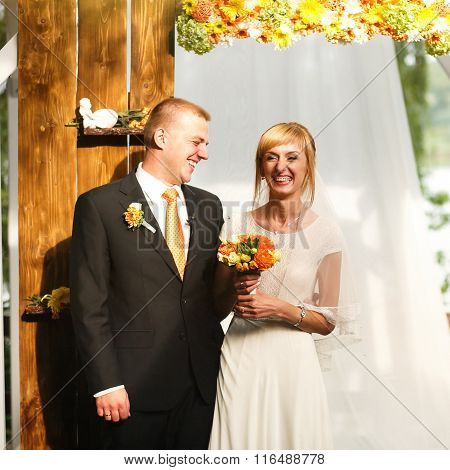Gorgeous Stylish Happy Bride And Groom Standing Near Orange Wooden Arch For A Wedding Ceremony