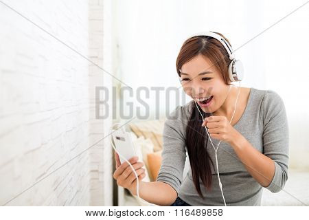 Asian Woman excited about the muisc on music player