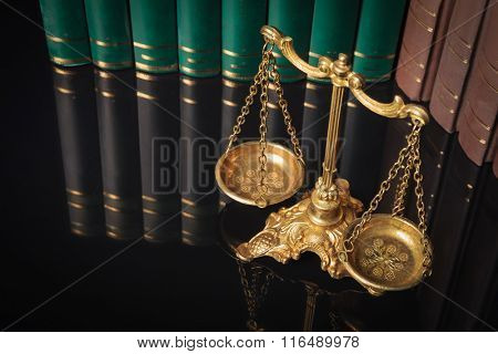 above picture of a golden justice scales in front of law books