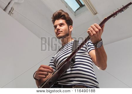 portrait of rock artist taken from below upward while playing the guitar and looking away
