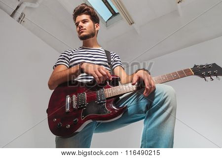 studio portrait from below upward of young guitarist pose with leg up, holding guitar while looking away