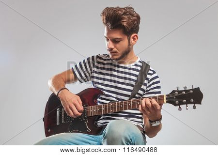 guitarist pose seated in studio background while playing guitar with eyes closed
