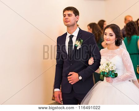 Bride and groom are holding each other's hands during wedding ceremony