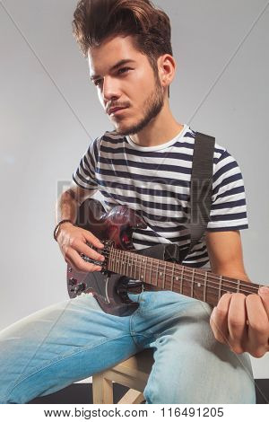 young guitarist posing in studio background while playing his instrument looking away. he is seated on chair.