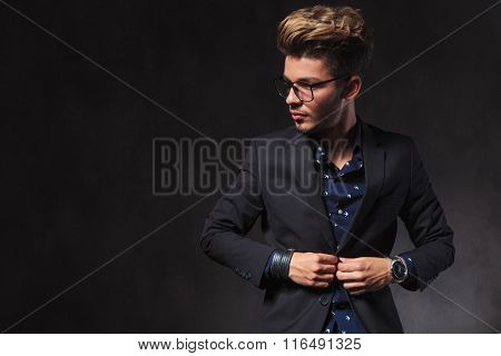 portrait of elegant man fixing his jacket in dark studio background. he is wearing glasses while looking away.