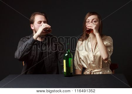 Man And Woman Are Boozing, Bottle On The Table, Keeping Glasses.