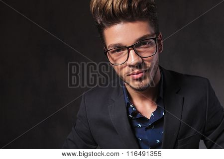 portrait of fashionable smart man wearing glasses in dark studio background looking at the camera