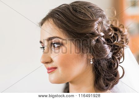 Beautiful young bride with wedding makeup and hairstyle in bedroom, newlywed woman final preparation