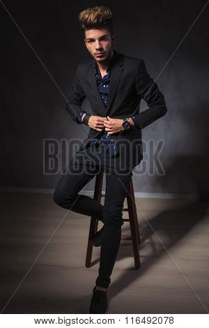 portrait of attractive elegant guy posing seated in dark studio background while fixing his jacket